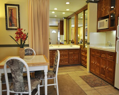 An open plan wooden dining alongside kitchen and sink vanity.