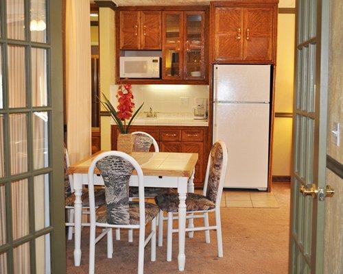 An open plan wooden dining alongside kitchen.