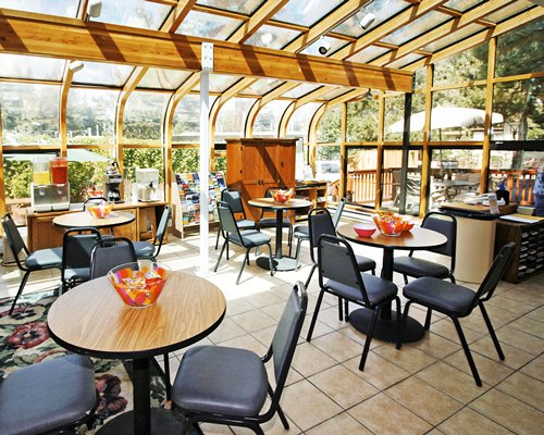 A restaurant with multiple dining tables and an outside view.