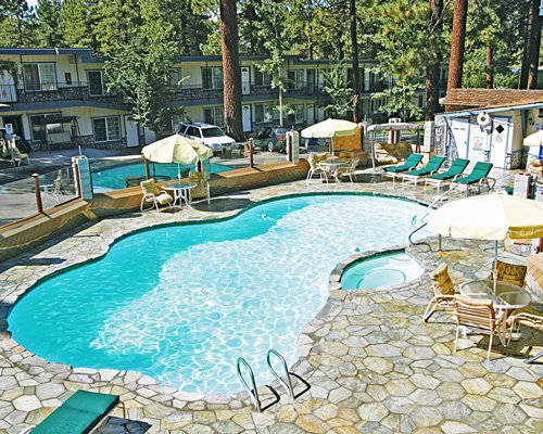 Outdoor swimming pool with chaise lounge chairs and patio furniture surrounded by woods.