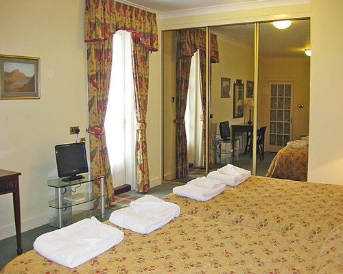 A well furnished bedroom with two double beds and a television.