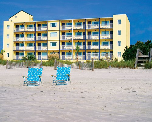 A beach view of chaise lounge chairs alongside multi story condo balconies.