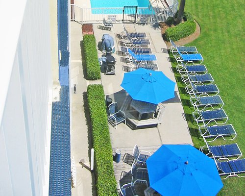 An aerial view of outdoor swimming pool with sunshades and chaise lounge chairs.