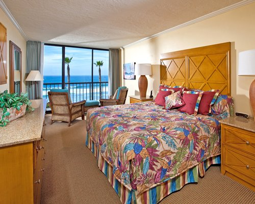 A furnished bedroom with a king bed and balcony with an ocean view.