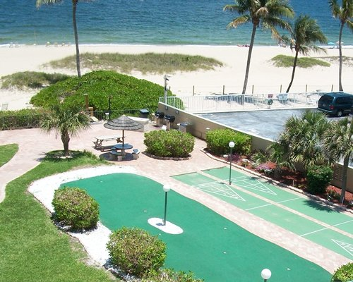 Scenic outdoor shuffle boards and golf course alongside beach.
