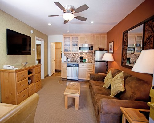 An open plan living room with kitchen and a television.