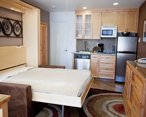 An open plan kitchen with telephone and a murphy bed.