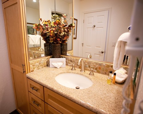 An open sink vanity with flower vase.