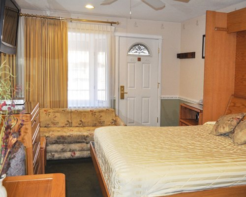 A well furnished bedroom with a murphy bed and a double pull out sofa.