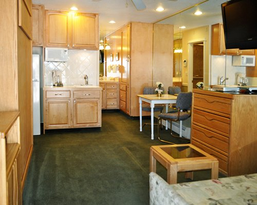 An open plan kitchen dining room and living area with a television.