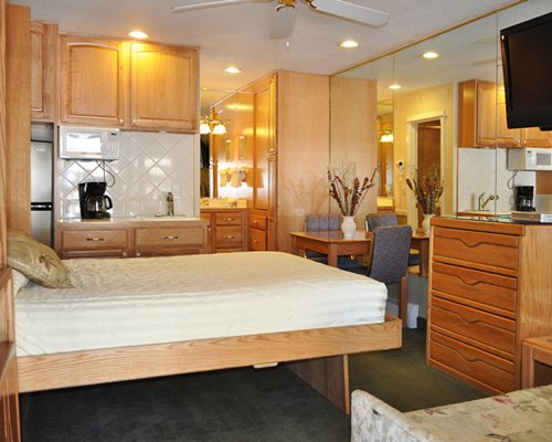 An open plan dining kitchen and murphy bed with a television.