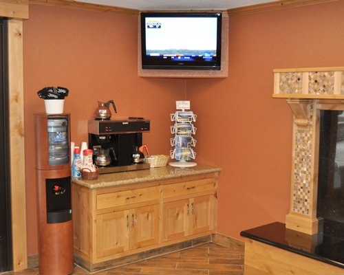 A well furnished common room with a coffee maker and a television.