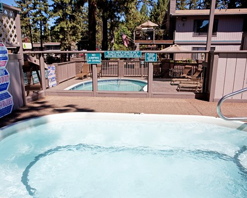 Two outdoor hot tubs with chaise lounge chairs.