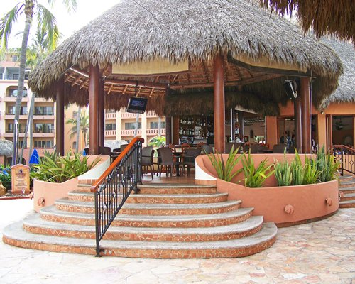 Bar with a television under a thatched sunshade.