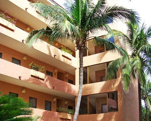 A view of multi story building surrounded by palm trees.