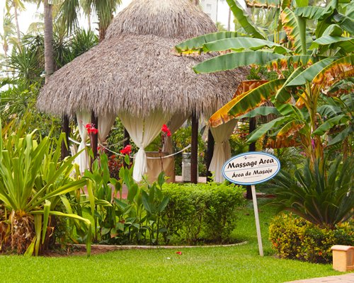 Scenic view of massage area under thatched sunshades.