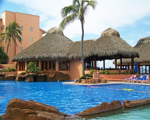An outdoor swimming pool with pool volleyball net alongside thatched sunshades.