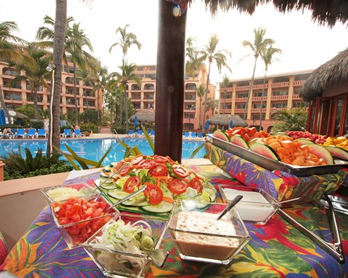 Salad and fruit dishes on a table alongside swimming pool.