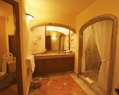 A bathroom with standing shower and a single sink vanity.