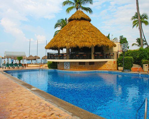 An outdoor swimming pool with thatched sunshades and a large gazebo.