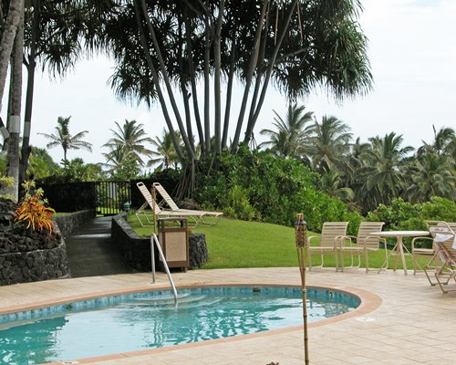 A scenic outdoor swimming pool with chaise lounge chairs.