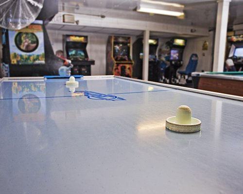 Indoor recreation room with air hockey pool table and arcade games.