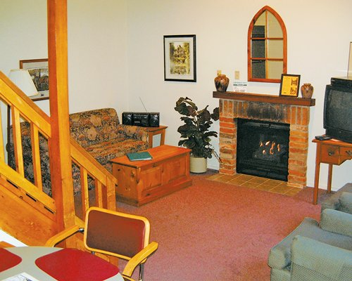 Furnished living room with dining television and a fire in the fireplace.