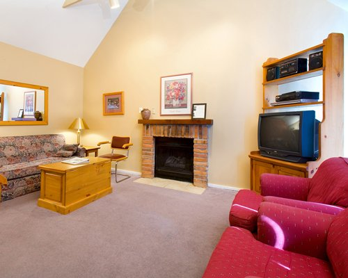A well furnished living room with fireplace and a television.