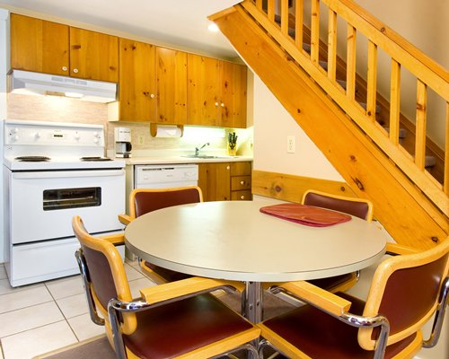 An open plan kitchen with dining area and wooden stairway.