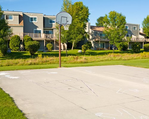 A scenic outdoor basketball court alongside multi story villas.