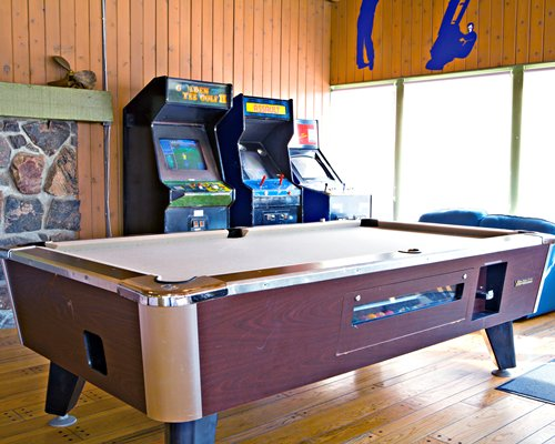 Indoor recreation room with pool table and arcade games.