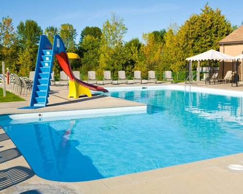 An outdoor swimming pool with kids water slide and chaise lounge chairs surrounded by wooded area.