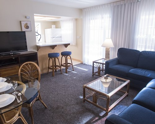 A well furnished open plan living room with television dining room and breakfast bar.