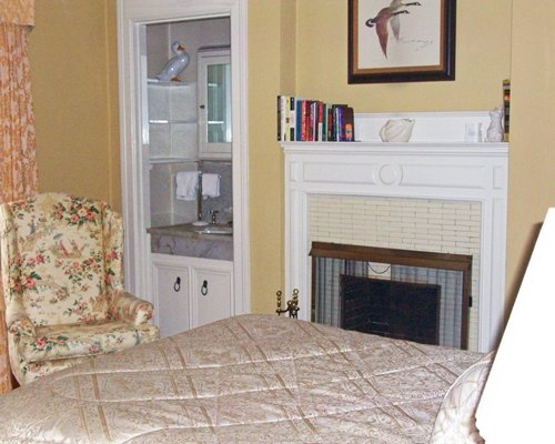 A well furnished bedroom with queen bed fireplace and vanity.