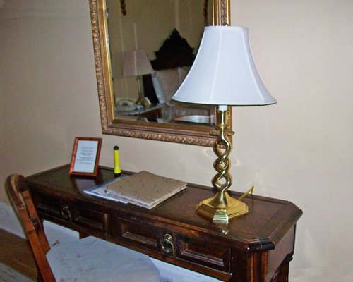 A study table with a lamp and mirror.