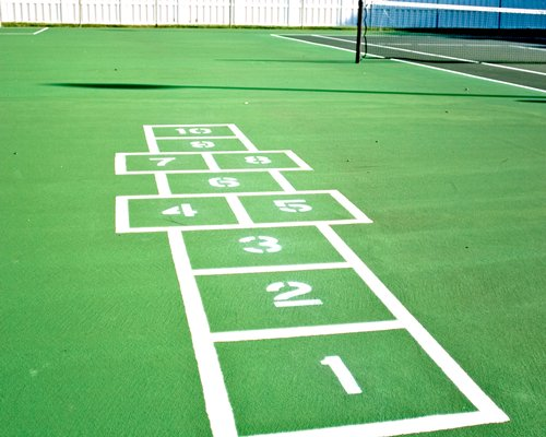 Outdoor play area with hopscotch and tennis court.