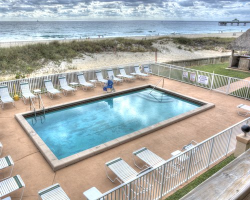 An outdoor swimming pool with chaise lounge chairs overlooking a beach.