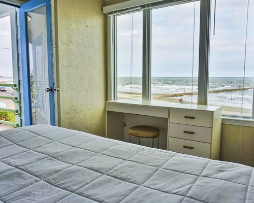 Furnished bedroom with queen bed and ocean view.