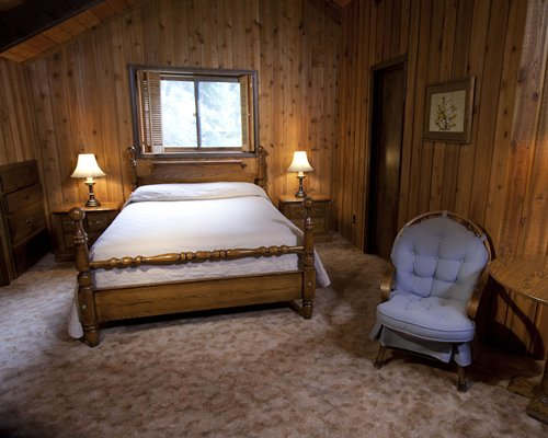 A wooden themed bedroom with a queen bed.