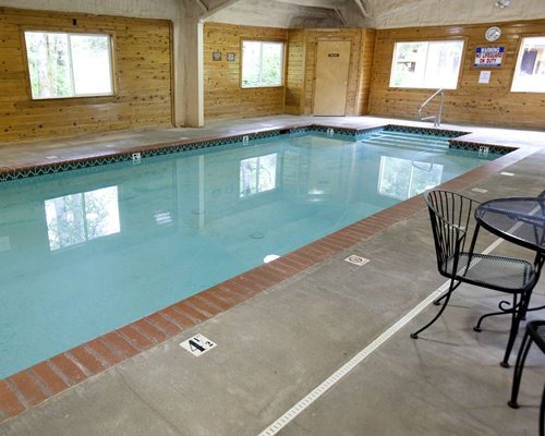 An indoor swimming pool with patio chairs.