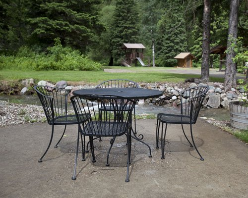 Outdoor patio furniture alongside a stream and wooded area.