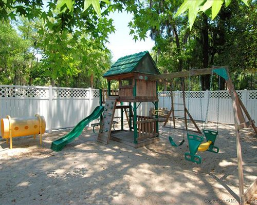 An outdoor play area surrounded by a wooded area.