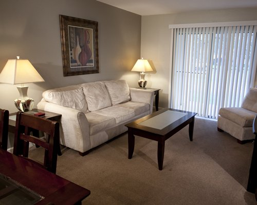 A well furnished living room with open plan dining area and outdoor view.