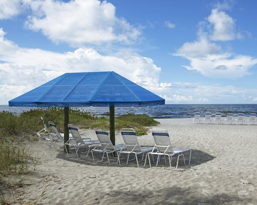 A beach view of chaise lounge chairs under a sunshade facing the ocean.