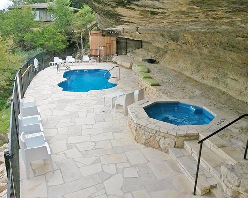 An outdoor swimming pool and hot tub with patio furniture.