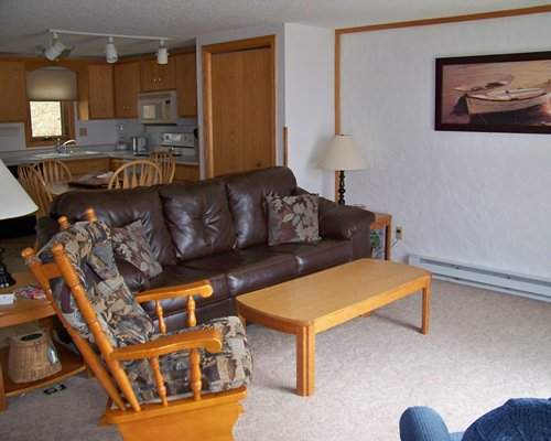 An open plan furnished living dining and kitchen area.