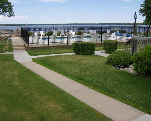 A pathway leading to the beach alongside an outdoor swimming pool.