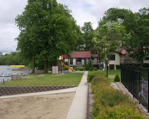 Scenic pathway leading to the resort with recreational area alongside lake.