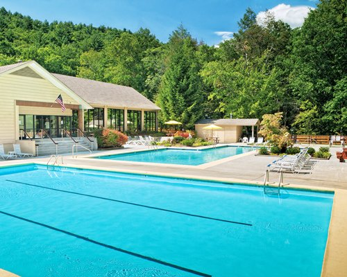 An outdoor swimming pool with chaise lounge chairs surrounded by wooded area.