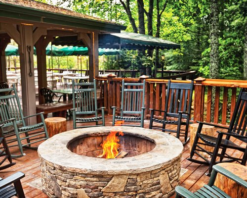 An outdoor fireplace surrounded by patio furniture.